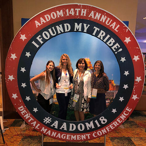 A giant circular AADOM sign with four of our board members standing in the middle