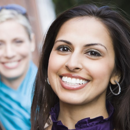 Close-up of a woman smiling with another woman behind her