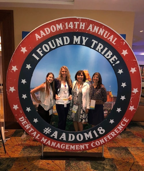 Some members of our team standing behind the AADOM 2018 circular sign
