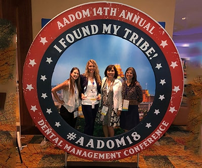 Big circular sign with four female members stood in the middle and smiling