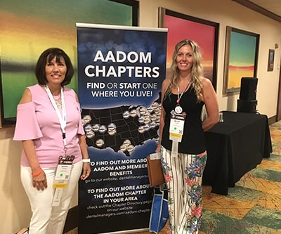 Two of our team standing either side of an AADOM Chapters sign