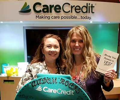 Two woman standing in front of a CareCredit logo and smiling